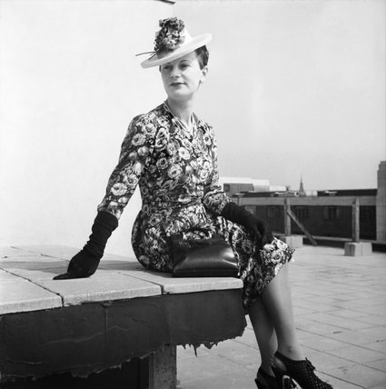A model sits on a low wall on a Bloomsbury rooftop to show off her pre-war printed silk dress.  According to the original caption, this dress has been