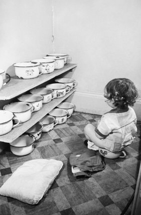 A young boy sits on his potty at the 'Foster Parents Plan for War Children' Nursery in Hampstead.  The chamber pots of the other children can be seen on shelves in the background.