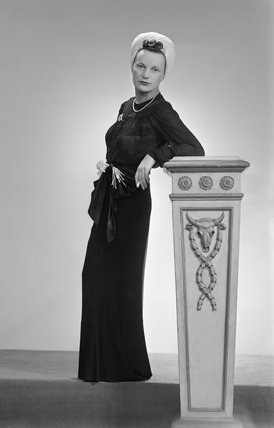 This photograph shows a model wearing an outfit which illustrates the way in which old clothes can be re-worked and worn as new.  The model, seen here leaning on an ornate plinth, wears a black chiffon blouse made from an old dinner dress, a long black sk