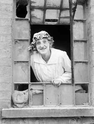 A striking portrait of a smiling female miller, her face covered in flour, as she looks out through an open window at a large mill, somewhere in Britain.