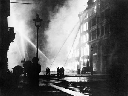 Members of the London Fire Brigade train their hoses on burning buildings in Queen Victoria Street, EC4, after the last and heaviest major raid mounted on the capital during the 'Blitz'.
