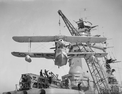 A Supermarine Walrus amphibious aircraft is hoisted on to the catapult on board HMS RODNEY prior to launch. The battleship's superstructure can be seen in the background.