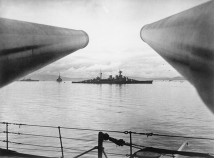 HMS HOOD seen between two 16 inch guns (belonging to HMS RODNEY) as she returned from the Mediterranean.