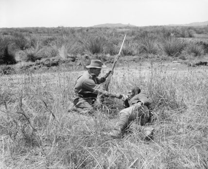 An Australian infantryman gives a drink to a wounded Turkish soldier during the Gallipoli Campaign in 1915.