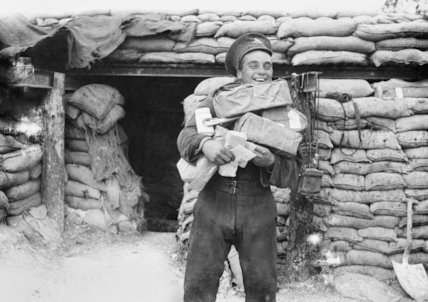 A smiling artilleryman with the post for his battery, near Aveluy, Somme, September 1916.
