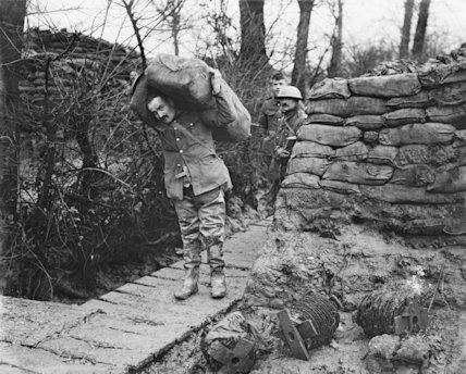 Lancashire Fusilier wearing waders taking a load of sandbags up a communication trench. Ploegsteert Wood, January 1917.
