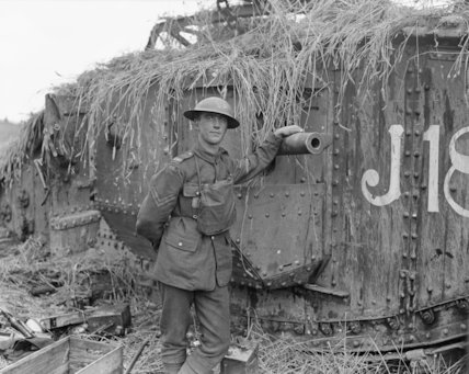 A British Army corporal stands beside the camouflaged Mark V Tank 'J18' in a cornfield near Albert, 1918.
