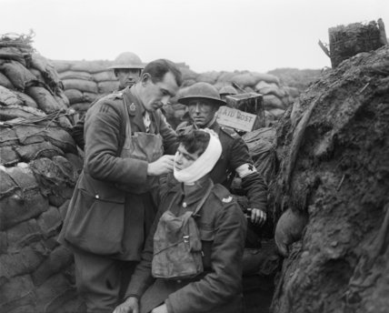 The Medical Officer bandaging the face wound of a man of his battalion in the line in the Arleux Sector, near Roclincourt, 9 January 1918.