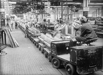 A woman drives a trolley train across a busy factory floor at the National Filling Factory, Chilwell.