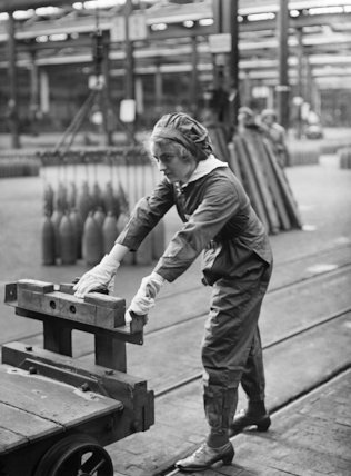 Girl worker pushing a trolly, in a shell filling factory.