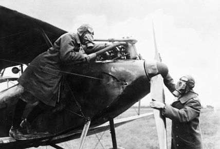 German Airmen, wearing gas masks, getting their machine ready to start again after a forced landing in a gas-affected area.