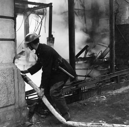 A fireman dampens down the flames after a raid, London, 1940