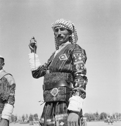 A new Assyrian recruit to the Iraq Levies adopts a warlike pose for the camera at RAF Habbaniyah, Iraq, 1942