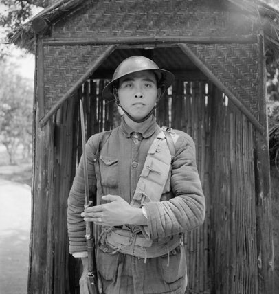 A Chinese sentry, wearing a British pattern steel helmet, stands guard at Pihu Military Training Centre, Fukien, China, 1944