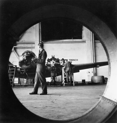 Ground crew overhaul the engine of a RAF Airspeed Oxford in a maintenance hanger, Britain, 1941