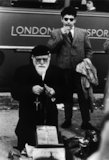 Two men on a street in front of London Transport bus: 1961