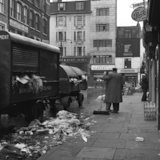 Man sweeping up rubbish in market. c.1955