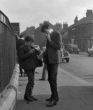 Two schoolboys standing by some railings. c.1955