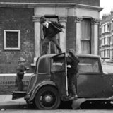 Three children play with a broken down car. c.1955