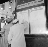 Passengers checking schedule at Kings Cross Station: 1955-1957