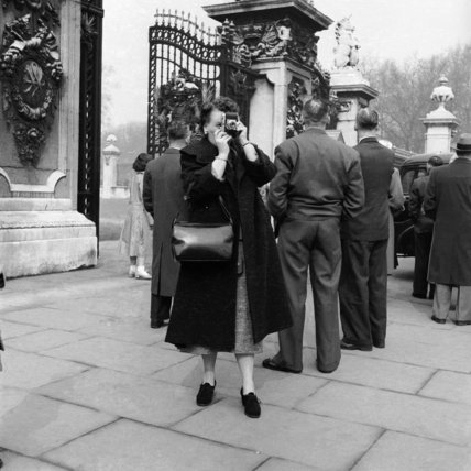A woman takes a photograph from outside the gates of Buckingham Palace; c1960