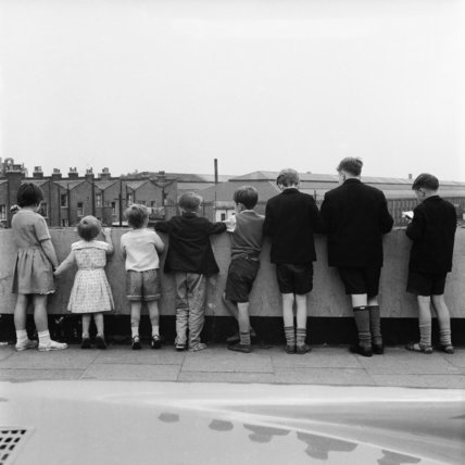 Girls and boys lined up on a bridge overseeing a railway line c.1960