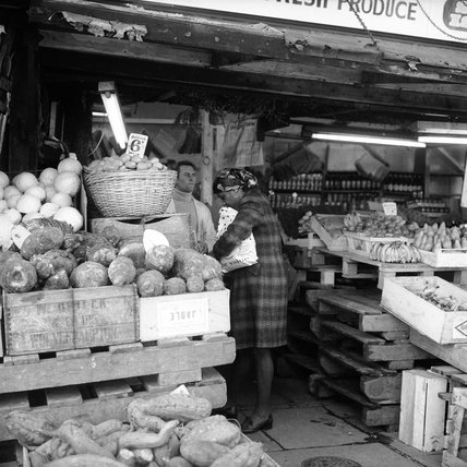 A lady shops for fruit and vegetables on display outside a shop; c.1965