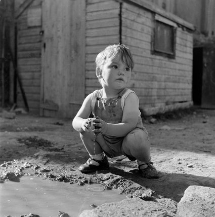 Young boy playing in a puddle; 1954