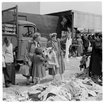 Women perusing clothes at a street market in Mile End: c.1948