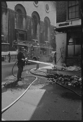 Fireman extinguishing flames at a building in Spitalfields: 1974