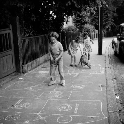 Girls playing hopscotch in the street; c.1955
