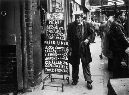 A man reads a chalk board on the street outside a cafe:1961