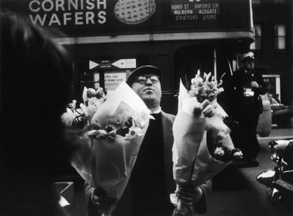 Man with bunches of flowers by a busy London road: 1961