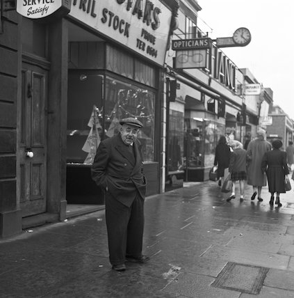 A man wearing a suit and cap standing in a high street. c.1955