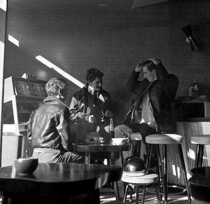 Three young men sit around a table inside a coffee bar. c.1955