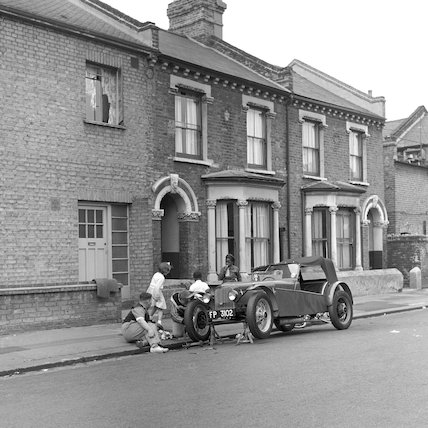 Two men working on a car at the side of a residential street. c.1955