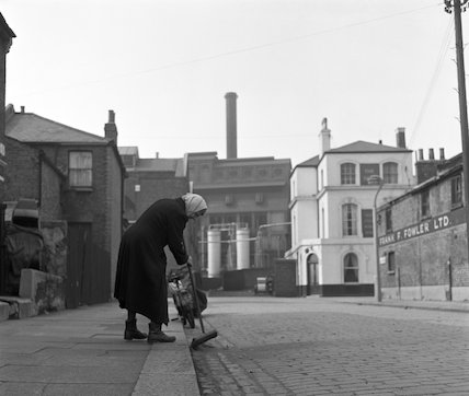 Woman sweeping kerb. c.1955
