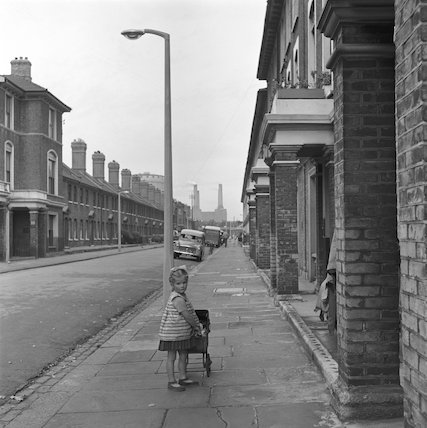 Girl playing with pram in street. c.1955