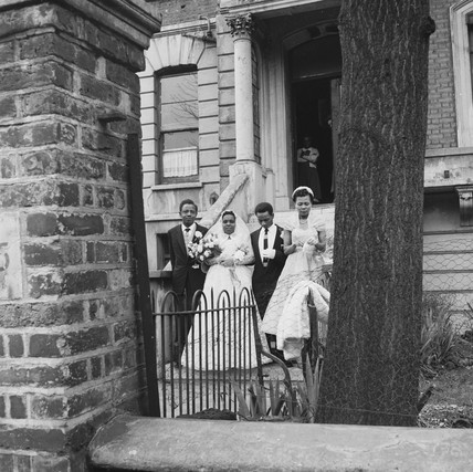 A wedding party pose for photographs: 20th century