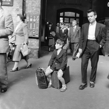 Boy sitting on the platform at Kings Cross Station: 1955-1957