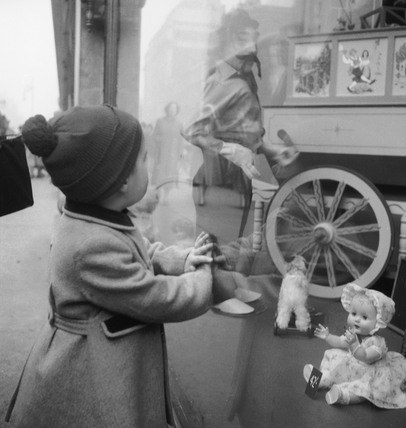 Toddler gazing into toy shop window: 1955