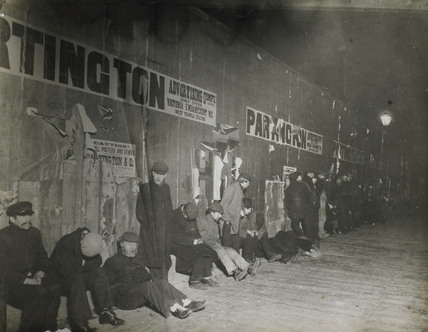 Unemployed men by a wall: c.1900