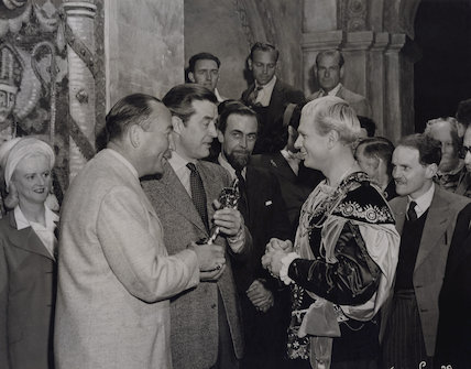 Hal Wallis and Ray Milland present Laurence Olivier with the Academy Award for 'Henry V' on the set of 'Hamlet'