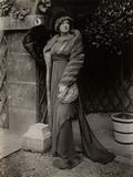 Model in fur coat and hat over a high-waisted dress, by Lucile