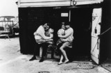 Two young couples seated outside a beach hut/garage, 1967.