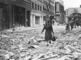 Woman walking along a bomb-damaged street i
