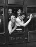 Women waving goodbye from a third class carriage window at Victoria Station.