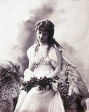 Young woman sitting on fur-covered seat holding a branch of leaves, c 1880-1899.