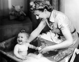 Woman bathing a baby, 1940s.
