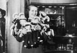 Woman holding doll sailors on-board the 'Queen Mary', 28 May 1936.